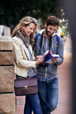 foreign: travel couple walking around city on vacation with guide book having fun