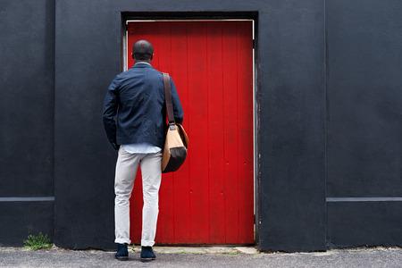 red door: african man standing at red door in city