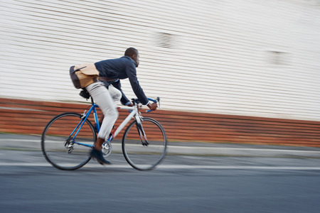 urban style: Black african mad riding bicycle in urban city commuting with speed and hipster trendy transportation