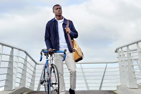clavados: moda joven hombre inconformista africano negro con la bicicleta que recorre en ciudad urbana en forma viaje al trabajo