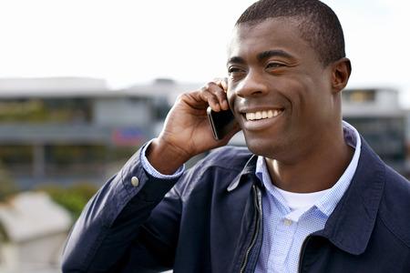 hombres negros: feliz joven hombre negro africano con el teléfono celular que tiene una conversación en el móvil Foto de archivo