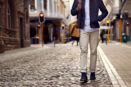 Young african man on vacation exploring european city cobblestone street Stockfoto