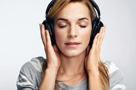 dj headphones: Portrait of young woman listening to music on dj headphones