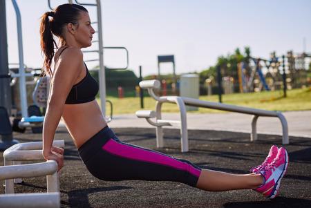 actividad fisica: mujer que trabaja en el gimnasio haciendo flexiones en el equipo divierten al aire libre