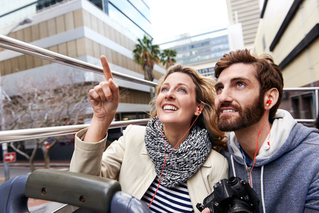 tourist guide: tourist couple on open top bus tour guide around the city in vacation
