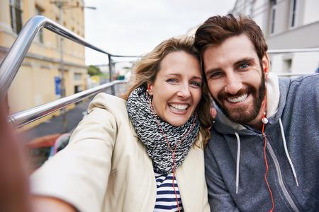 tourist couple travel selfie on open top tour bus in city Stockfoto