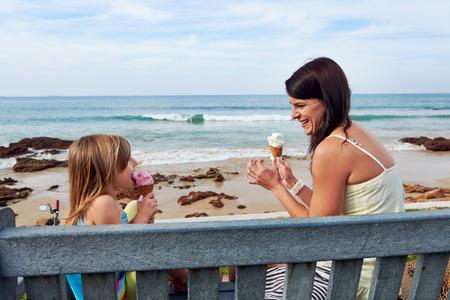 comiendo helado: Mam� e hija disfrutan de un helado de diversi�n en la playa sonriente riendo alegr�a en las vacaciones de verano Foto de archivo