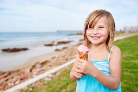 child ice cream: young girl enjoying ice cream at the beach on summer vacation