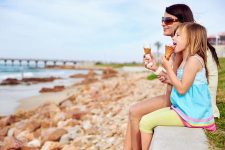 madre soltera: Mamá e hija disfrutan de un helado de diversión en la playa sonriente riendo alegría en las vacaciones de verano Foto de archivo