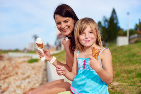 ice cream woman: Mom and daughter enjoy fun ice cream at the beach smiling laughing joy on summer vacation