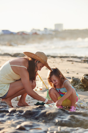 ocean fishing: Mother and daughter spend the day fishing at the beach together having fun and bonding over some qaulity parent childhood time Stock Photo