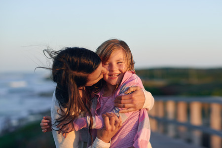 hugging: Unconditional love between mother and daughter hugging and embrace with a kiss and cuddle outdoors having fun