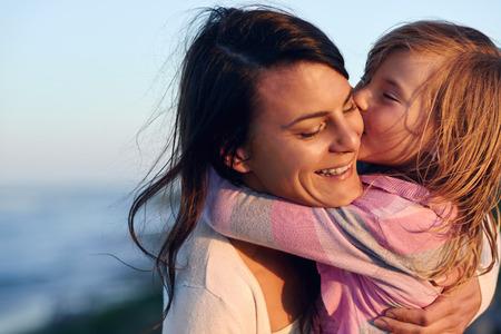 bacio: L'amore incondizionato tra madre e figlia abbracciare e abbracciare con un bacio e coccole che hanno divertimento all'aperto
