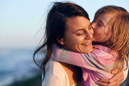 parenthood: Unconditional love between mother and daughter hugging and embrace with a kiss and cuddle outdoors having fun