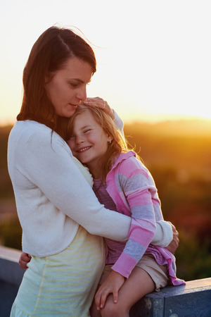 kids hugging: Unconditional love between mother and daughter hugging and embrace with a kiss and cuddle outdoors having fun