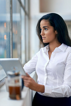 Young business woman investor using tablet computer for work in office with coffee photo