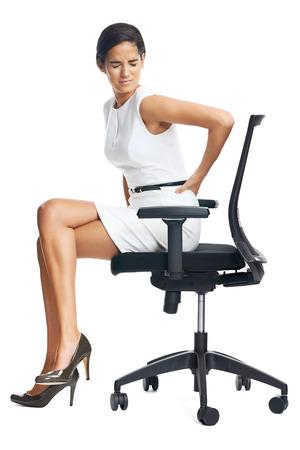 Zakenvrouw met lage rugpijn van het zitten op bureaustoel Stockfoto