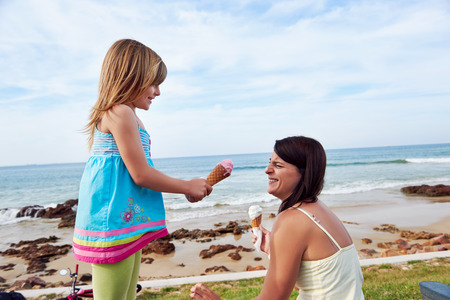 Mom and daughter enjoy fun ice cream at the beach smiling laughing joy on summer vacation photo