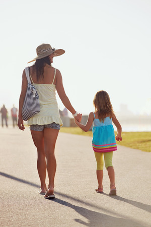 social responsibility: Mother and Daughter walking together at the beach holding hands in summer