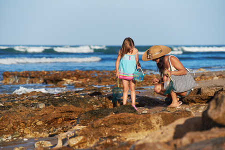 Mother and daughter spend the day fishing at the beach together having fun and bonding over some qaulity parent childhood time Imagens
