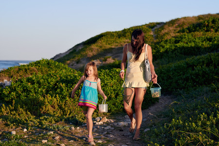 family activities: Mom and daughter walking after going fishing at the bach on a summer afternoon Stock Photo