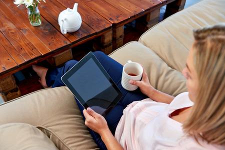 女性自宅がタブレット コンピューター wifi 接続でメールを読んでソファー ソファでリラックス 写真素材