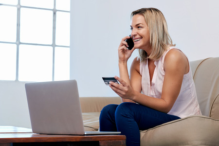 Woman sitting on sofa couch checking accounts and shopping online at home photo