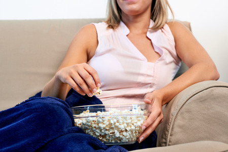 bowl of popcorn: woman relaxing with a bowl of popcorn while watching t.v. on sofa couch