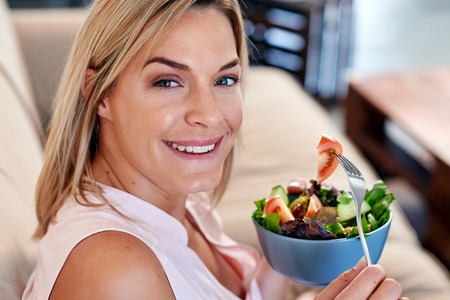tomato  salad: Retrato de mujer disfrutando de un plato de ensalada saludable en el hogar