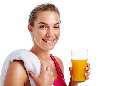 Woman getting ready for gym workout with towel and orange juice in studio photo