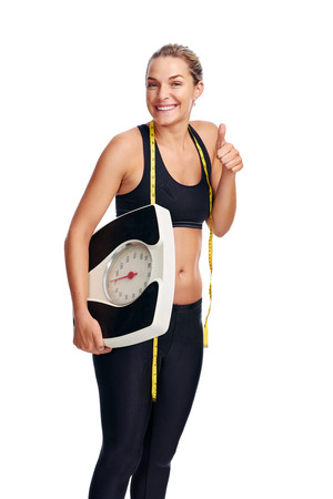 achieving: Women with scale cheering for achieving her weight loss goal isolated on white background