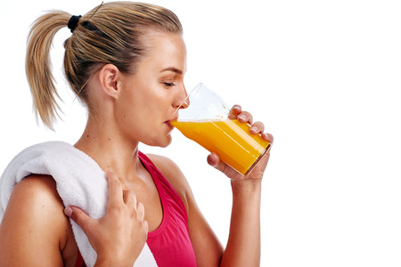 Woman getting ready for gym workout with towel and orange juice in studio Banque d'images