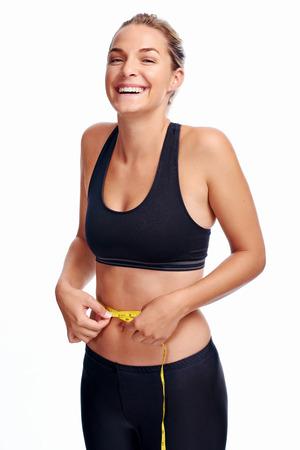 Donna che cattura misura della vita con nastro per il sottile dieta dimagrante sana weightloss