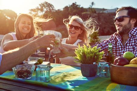 Grupo de brinde dos amigos para uma festa com bebidas, enquanto pendurado para fora em um restaurante em um terra�o na cobertura