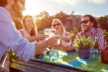 Grupo de brinde dos amigos para uma festa com bebidas, enquanto pendurado para fora em um restaurante em um terra