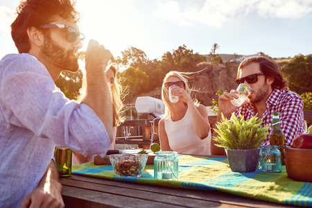 Skupina přátel sedí visí ven s nápoji na střeše