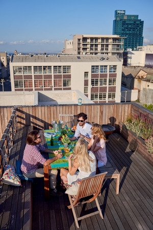 alfresco: Group of friends sitting hanging out with drinks on rooftop in urban city Stock Photo