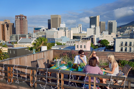 座っている友人のグループ都市の屋上でドリンクと一緒に出かける