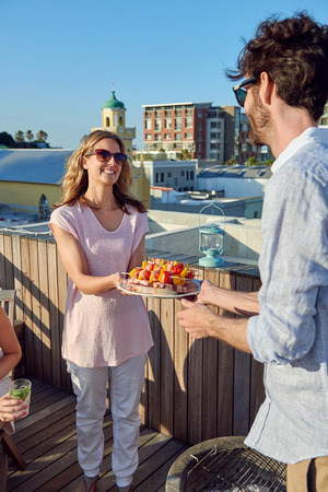 Friends having a barbeque on the outdoor rooftop with skewer kebabs photo