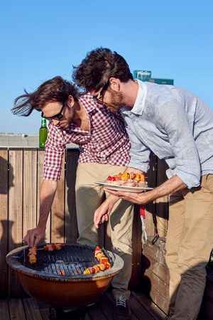 charcoal grill: Friends having a barbecue on outdoor rooftop terrace with skewer kebabs