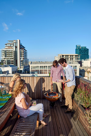 Friends having a barbeque on the outdoor rooftop terrace with skewer kebabs Stock Photo