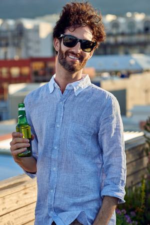 lifestyle caucasian: portrait of young man standing outdoors on rooftop terrace with beer