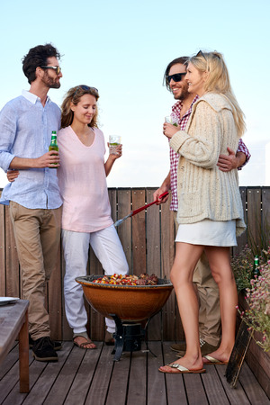 rooftop: Couples having a barbeque on the outdoor rooftop terrace with skewer kebabs