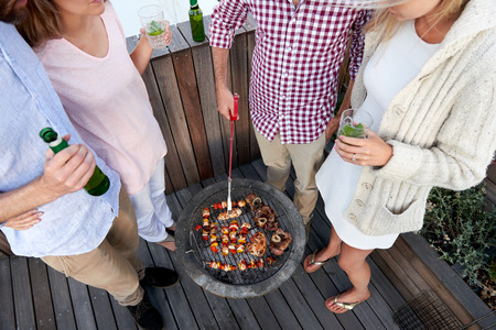 Couples having a barbeque  skewer kebabs outdoors photo