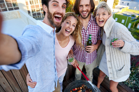 Group of friends taking a selfie at their outdoor rooftop barbeque