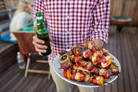 Man serves skewer kebabs for outdoor barbeque dinner party holding beer Stock Photo