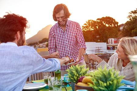 fiesta amigos: Hombre sirve amigos pincho kebab en la azotea al aire libre cena barbacoa