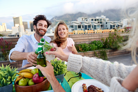 rooftop: Group of friends toasting to a celebration with drinks while hanging out at a restaurant on a rooftop terrace