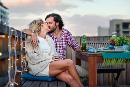 romantic kiss couple at rooftop barbecue evening