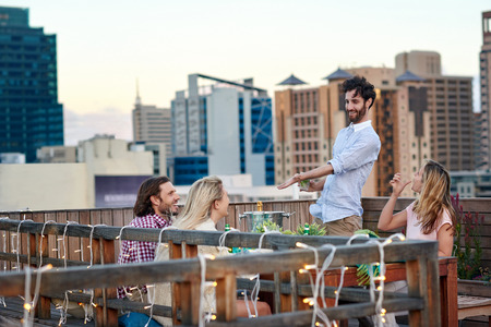 Man making a toast to his friends proposal celebration outdoor on rooftop terrace